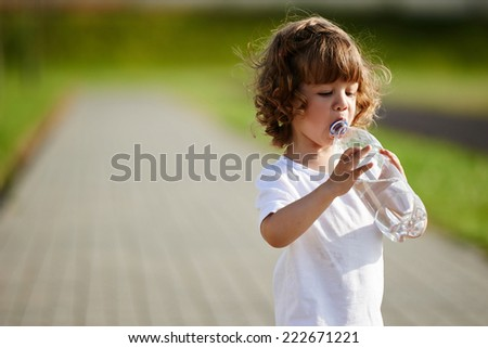 little girl drinking clean water from bottle - stock photo