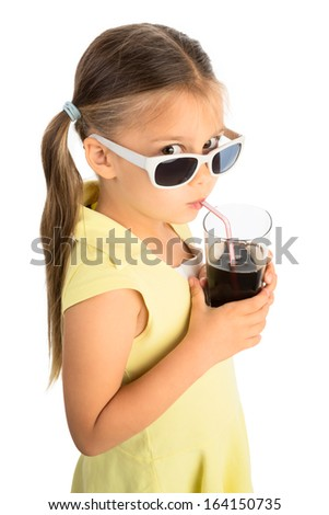 Little girl drinking cola beverage through a straw and looking at viewer over sunglasses skeptically, seen from high vantage point - stock photo