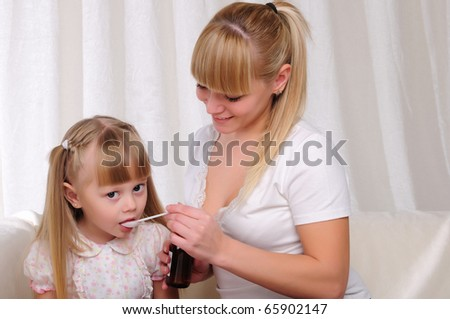 Little girl drinking cough syrup with a small spoon from the hands of moms