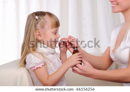 Little girl drinking cough syrup with a small spoon from the hands of moms - stock photo