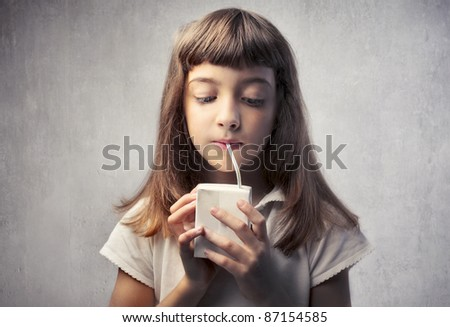 Little girl drinking fruit juice - stock photo