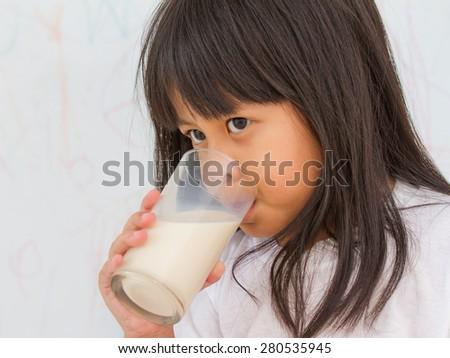 little girl drinking glass of milk - stock photo