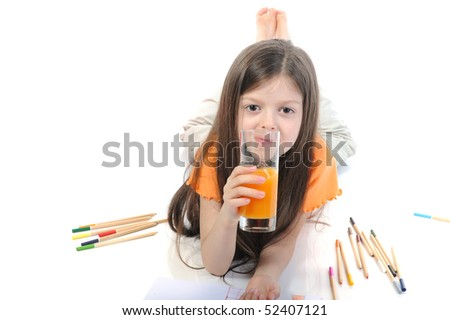 Little girl drinking juice from a glass lying on the floor. Isolated on white background