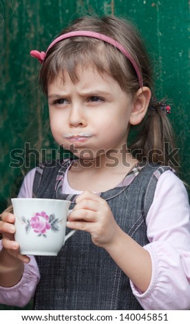 Little girl drinking milk out of cup.  A milk mustache has formed on her upper lip - stock photo