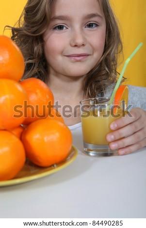 Little girl drinking orange juice - stock photo