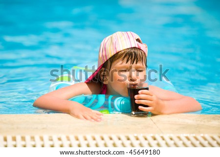 Little girl drinking soda in pool summer holidays - stock photo