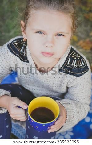 Little girl drinking tea outdoors - stock photo