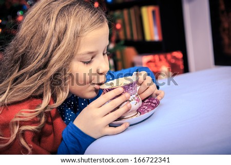 little girl drinking tea with xmas cookies at home - stock photo