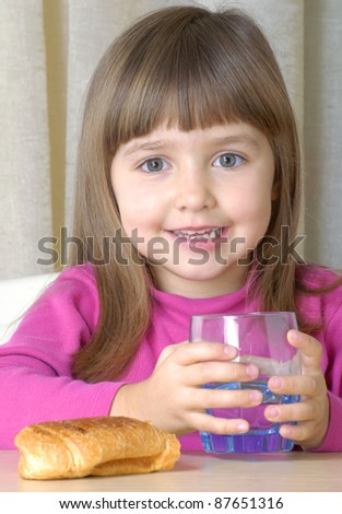 Little girl drinking water and eating croissant. - stock photo