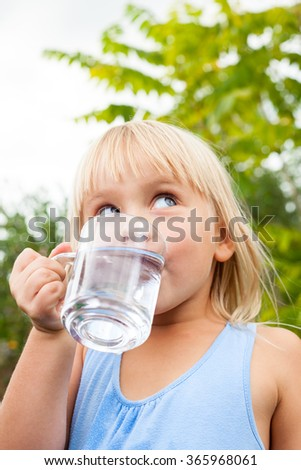 Little girl drinking water looking side in a summer garden