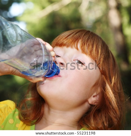 Little girl drinking water oudoors