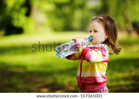 little girl drinks mineral water - stock photo