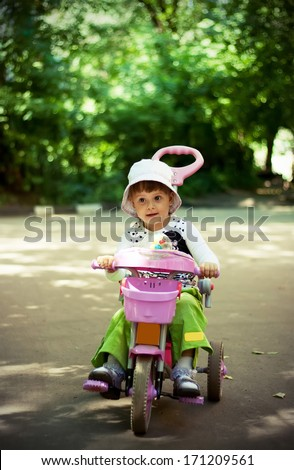 little girl driving her tricycle smiling - stock photo