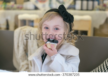 Little girl eat cake. curly blond 4 years old with blue eyes