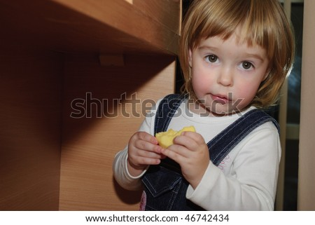 Little girl eat near the table. She hided and was surprised for you finded he - stock photo