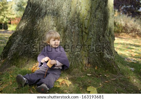 little girl eating a biscuit , outdoors in an autumn park