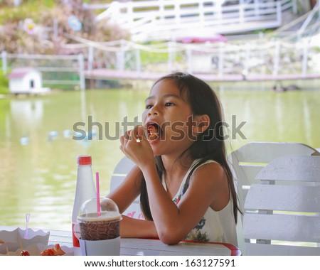 Little girl eating a hot dog.Kid eating hot dog - stock photo