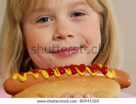 Little girl eating a hot dog.Kid eating hot dog. - stock photo