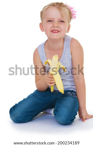 little girl eating a juicy banana. Isolated on white background - stock photo