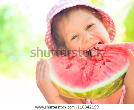 little girl eating a ripe juicy watermelon in summertime - stock photo