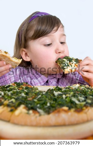 little girl eating a spinach pizza - stock photo
