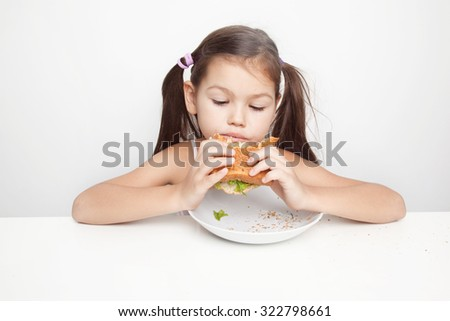 Little girl eating a vegan sandwich - stock photo