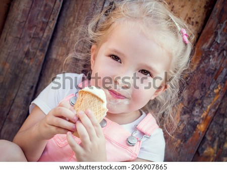 little girl eating an ice-cream in a wooden fence - stock photo