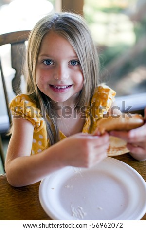 Little girl eating at the table - stock photo