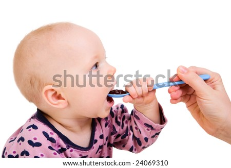 Little girl eating baby food with spoon. Isolated on white - stock photo