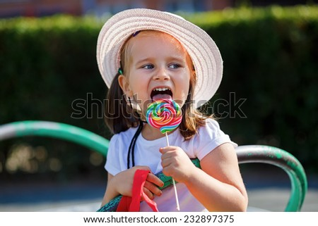 Little girl eating big candy. Shallow depth of field. - stock photo