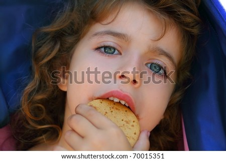 Little girl eating biscuit closeup face portrait