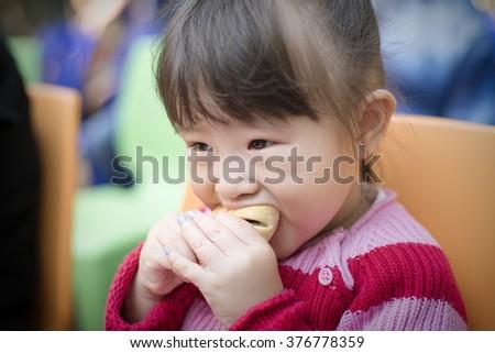 Little girl eating bread - stock photo