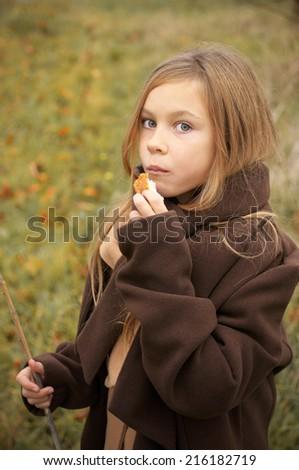 Little girl eating bread outdoors. - stock photo