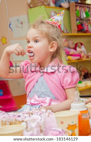 little girl eating cake on her birthday party