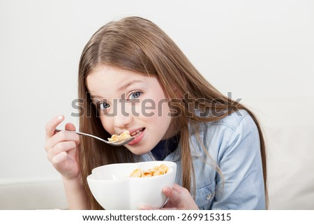 Little girl eating cereal in the breakfast