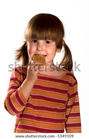 Little girl eating cookie wearing casual striped closes isolated on white - stock photo