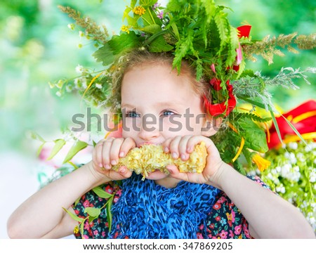 Little girl eating corn with a wreath of grass on her head, picnic - stock photo