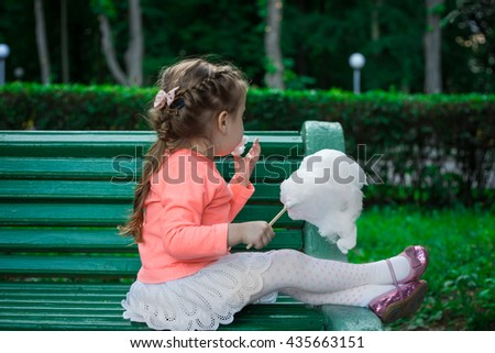 little girl eating cotton candy while sitting on a Park bench - stock photo