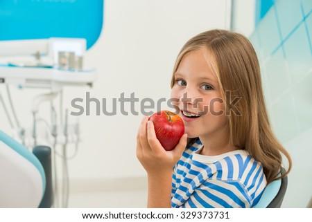 Little girl eating fresh apple in the office of dentist - stock photo