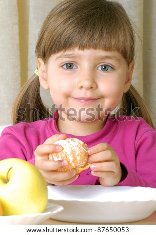 Little girl eating fresh tangerine - stock photo