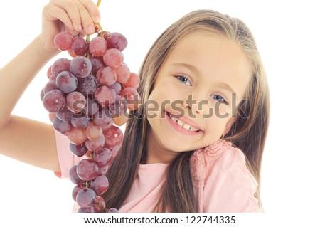 little girl eating grape - stock photo