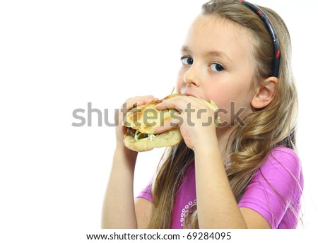 little girl eating hamburger isolated on white