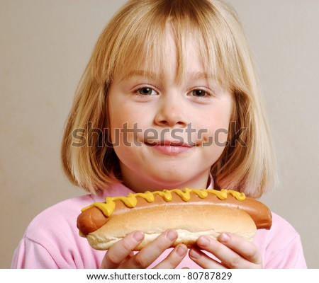Little girl eating hot dog,Kid eating hot dog. - stock photo