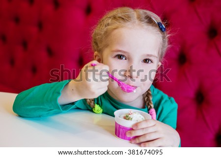 little girl eating ice cream in a cafe from the cup - stock photo