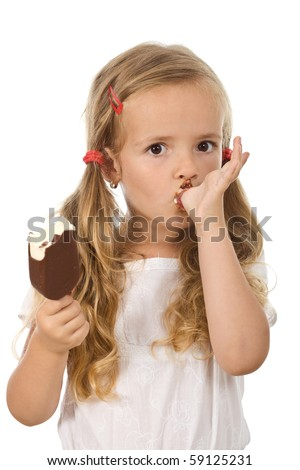 Little girl eating ice cream, licking her finger - isolated - stock photo