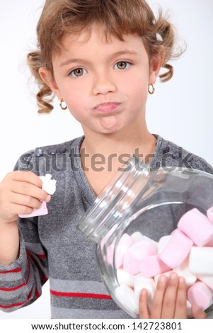 Little girl eating marshmallows from a jar - stock photo
