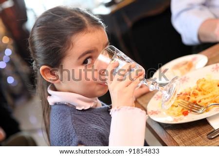 Little girl eating meal in restaurant - stock photo