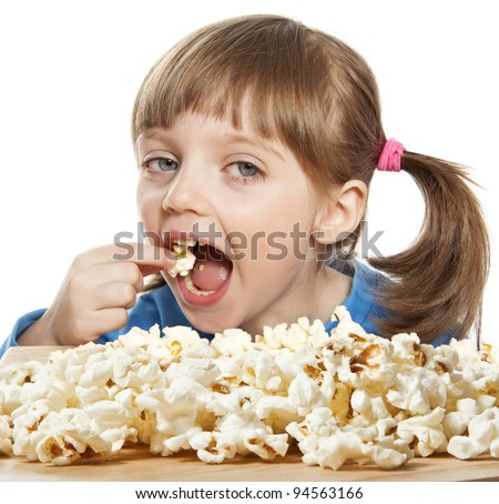 little girl eating popcorn isolated - stock photo