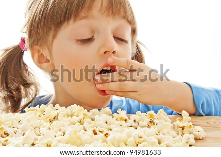little girl eating popcorn isolated on white background - stock photo