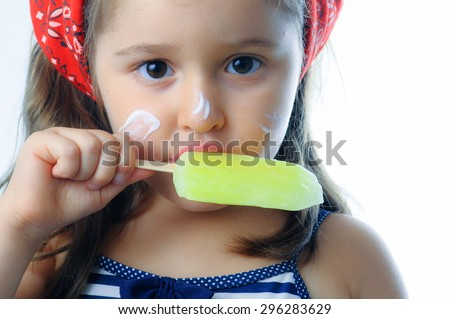 Little girl eating popsicle indoor. Little girl licking a ice lolly. - stock photo